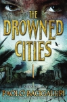 Book cover for The Drowned Cities - a person's eyes over a dark city with a gold citadel in the center