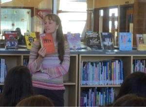 A white woman with long hair stands in front of low bookshelves topped with face-out books. She is holding a book and talking about it to a group of students who are facing away from the camera.