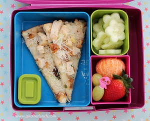 A cute, brightly-colored bento-style packed lunch with pizza, cucumber cut into a flower shape, and fruit