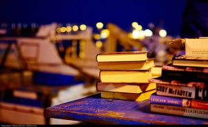 books stacked on top of a table outdoors at dusk with lights in the background