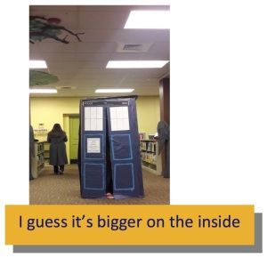 A cardboard TARDIS with the foot of someone inside visible
