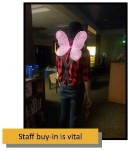 A view from behind of someone wearing a red plaid shirt, jeans, and pink fairy wings