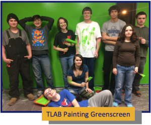 A photograph of students standing in front of a green screen. Two students are holding paint brushes and a number of them have paint smeared on their faces and clothes.