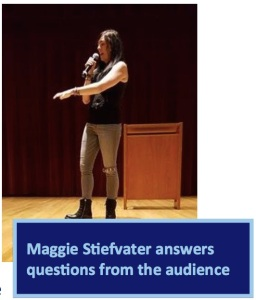 Author Maggie Stiefvater stands on a stage, pointing